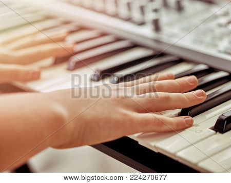 Midi keyboard or electronic piano and playing child hands. Musical education for kid in music school.