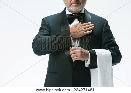The senior waiter holding white towel and standing isolated on white studio background. sign language in the restaurant. Gesture means - come to me partner