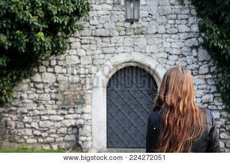 The young girl turned her back on the background of stone walls and vintage doors