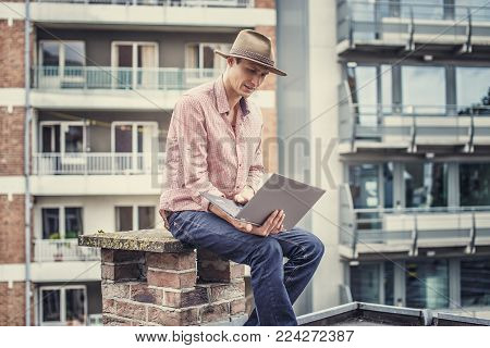 Man in hat with laptop. Multifamilly houses on background.