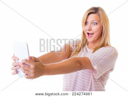 Surprised emotional young woman using tablet touchpad. Blond shocked girl reading e-book e-reader isolated. Technology.