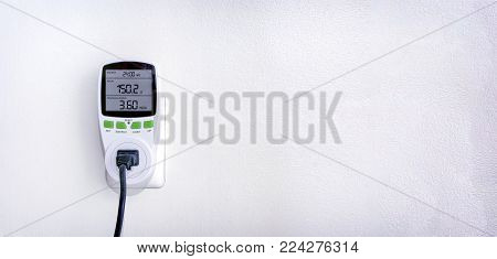 Watt Meter Plug in Operation on an Electrical Socket on the Wall