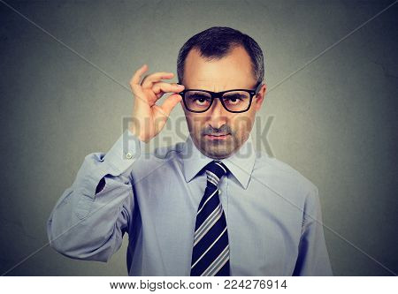 Skeptical middle aged business man looking at camera