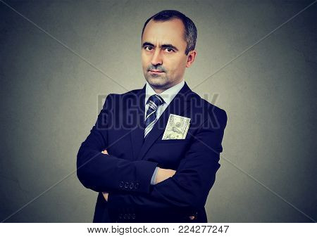 Businessman with one hundred dollar banknote in his jacket pocket