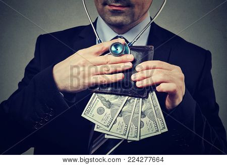 Businessman with stethoscope listening to wallet with dollar banknotes