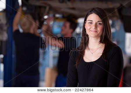 Um feliz feminino auto reparar cliente olhando para a câmera com um sorriso