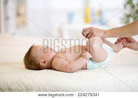 adorable baby newborn enjoying massage from mother