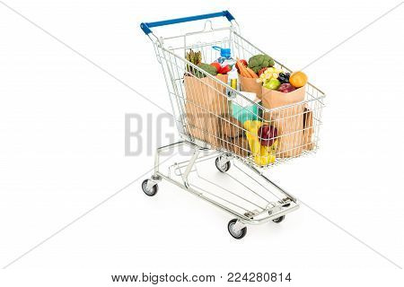 grocery bags in shopping trolley isolated on white