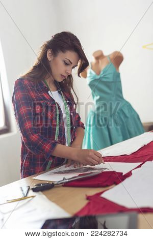 Seamstress drawing an outline of new dress design on a fabric with a piece of chalk