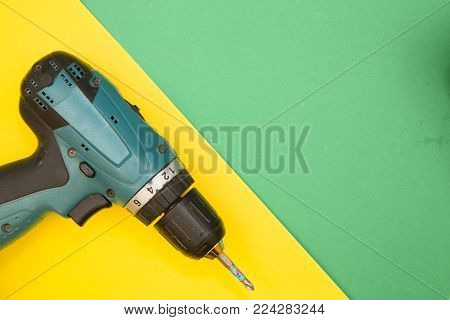 Home, House Repair, Redecorating, Renovating Concept. A drill on a bright yellow and green background with copy space, top view, flat lay