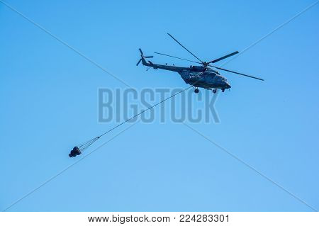 ROSTOV-NA-DONU, RUSSIA - CIRCA SEPTEMBER 2017: Russian military helicopter with water bucket in sky at military air show