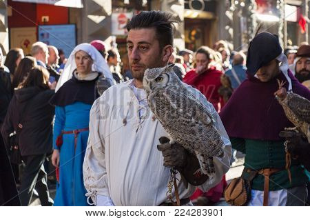 Italy, Florence - January 6 2017: the view of the man in medieval costume holding an owl at traditional parade of Epiphany Befana, medieval festival in Florence on 6 January 2017, Florence, Tuscany, Italy.