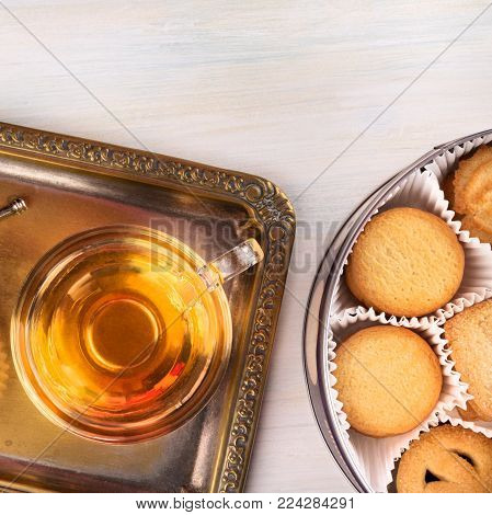 An overhead square photo of Danish butter cookies with a cup of tea on a vintage tray, and a tin can, shot from above with a place for text