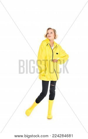 dreamy young woman in stylish yellow raincoat and rain boots isolated on white