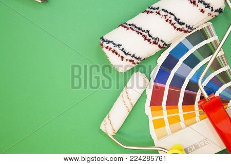 Painting house, Home, Appartment Concept. A set of repair tools: Color range palette of household paint and wall coating and paint rollers on a green background, top view, flat lay.