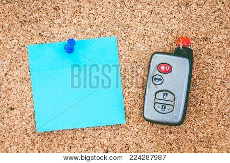 Car key and paper on cork board