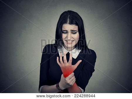 Young woman holding her painful wrist colored in red  isolated on gray wall background. Sprain pain