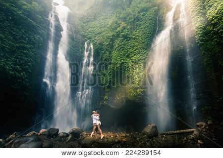 Amazing romantic view of happy couple near beautiful grand waterfall in jungles mountain. A man making proposal to his girlfriend. Success life. Marriage couple outdoor