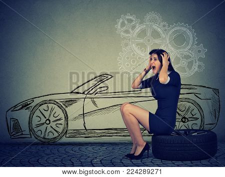 Stressed woman with broken down car flat tire in the middle of the street