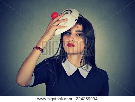 Young woman taking off a mask. Pretending to be someone else concept