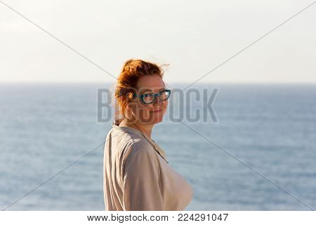 Ginger woman in her forties by the seaside