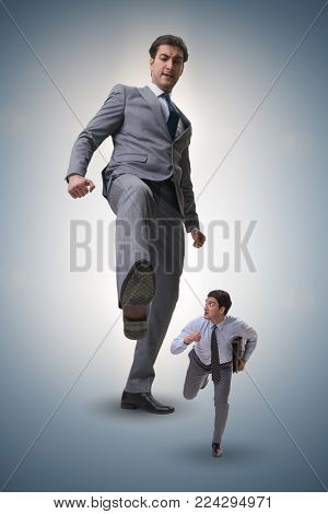Bad angry boss kicking employee in business concept