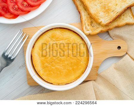 white round ramekin with oven-baked omelet of eggs and milk, with a crust, on white wooden table, top view.