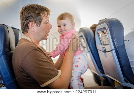 Young tired father and his crying baby daughter during flight on airplane going on vacations. Dad holding baby girl on arm. Air travel with baby, child and family concept.