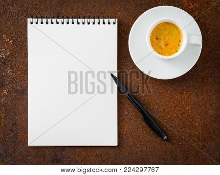 white empty blank sheet of notebook with a spiral, pencil and cup of coffee on rusted old iron table, top view.