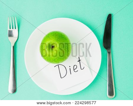 Ripe raw juicy green Apple, slip of paper with inscription diet on a white plate, fork, knife on a bright turquoise blue colour table, top view. Diet as lifestyle.