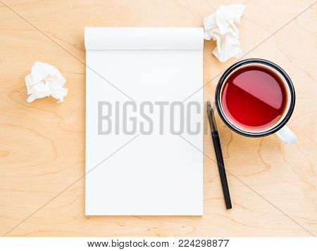 Open notebook with a white clean sheet for notes and drawing, wrinkled paper, pencil and mug of tea. Light wood background, top view.