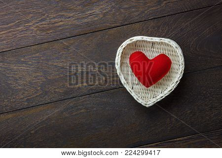 Table top view image of decoration valentine's day background concept.Flat lay heart shape and essential symbol love season with wood basket on modern rustic brown wooden at home office desk studio.