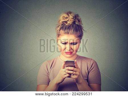 Sad upset woman using mobile phone isolated on gray wall background