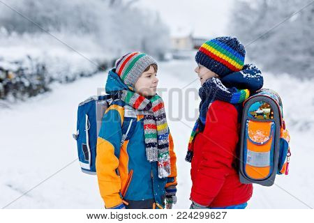 Two little kids boys of elementary class walking to school during snowfall. Happy children having fun and playing with first snow. Siblings ans friends with backpack in colorful winter clothes