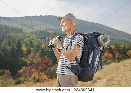 Elderly hiker holding a pair of binoculars and looking away outdoors