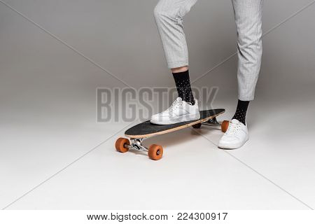 low section of stylish man standing on skateboard on grey