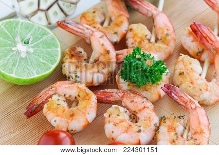 Skewers shrimp barbecue served on wood cutting board. Shrimps steak with lemon or lime and fresh cherry tomato. Delicious grilled prawn or shrimp with spices for snacks in party. Homemade food concept of seafood menu. Shrimp barbecue ready to served.