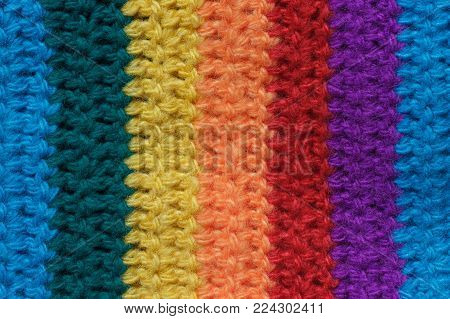 Texture of the knitted fabric. Crochet from yarn, handmade. A pattern of vertical strips of multi-colored yarn.