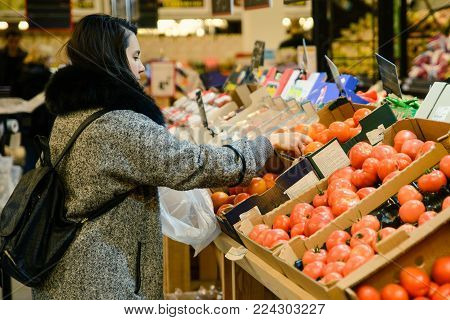 young woman choose tomatos in the store