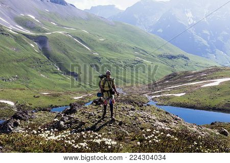 A traveler in the mountains against the backdrop of idyllic landscapes of alpine meadows with a lake. Lifestyle is active, hiking, tourism. Picturesque landscapes of the Alpine mountains in the summer season.