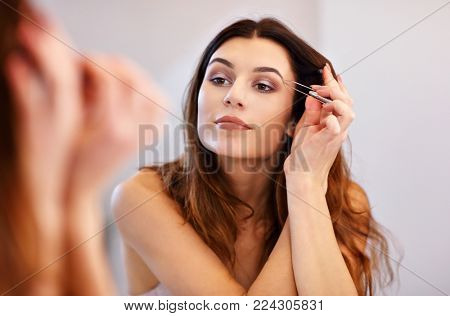 young woman doing make-up while looking at the mirror in bathroom