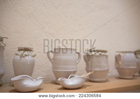 White Ancient Pots Of Ceramic On A Shelf.
