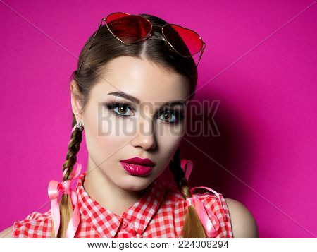 Portrait of young beautiful woman wearing heart shaped red glasses. Valentines day, love or theme party concept. Smokey eyes and red lips make up. Studio shot