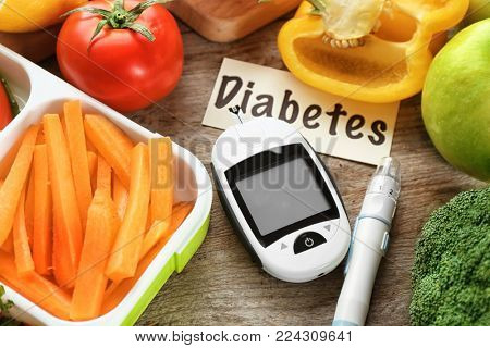 Digital glucometer, lancet pen and products on table. Diabetes diet