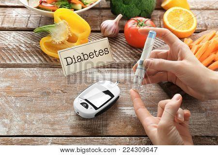 Woman using lancet pen near digital glucometer, closeup. Diabetes diet