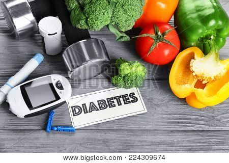 Composition with digital glucometer, vegetables and dumbbells on table. Diabetes diet