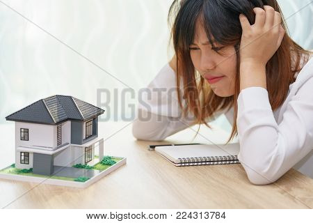 Stressed woman with running out of money in piggy bank and her house - dept and installment payment concept.