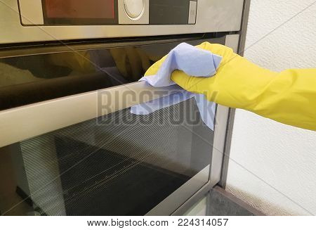 A female hand in yellow gloves washes the kitchen stove