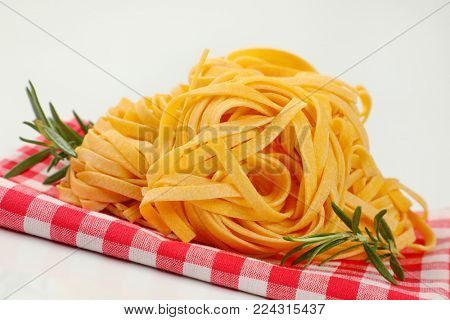 bundles of dried ribbon pasta on checkered place mat- close up
