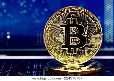 Bitcoin. Crypto currency Bitcoin, BTC, Bit Coin. Macro shot of Bitcoin golden coin on blue background and chart under. Blockchain